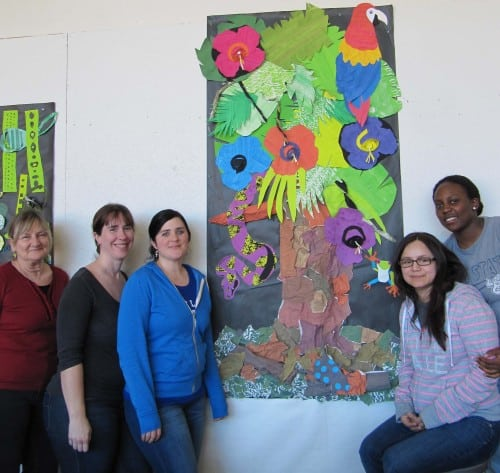 Teachers standing with artwork.