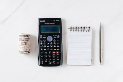 Photo of money, calculator, notepad and pen