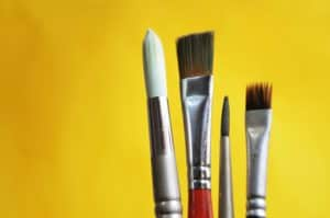 Image of various paintbrushes against a yellow background